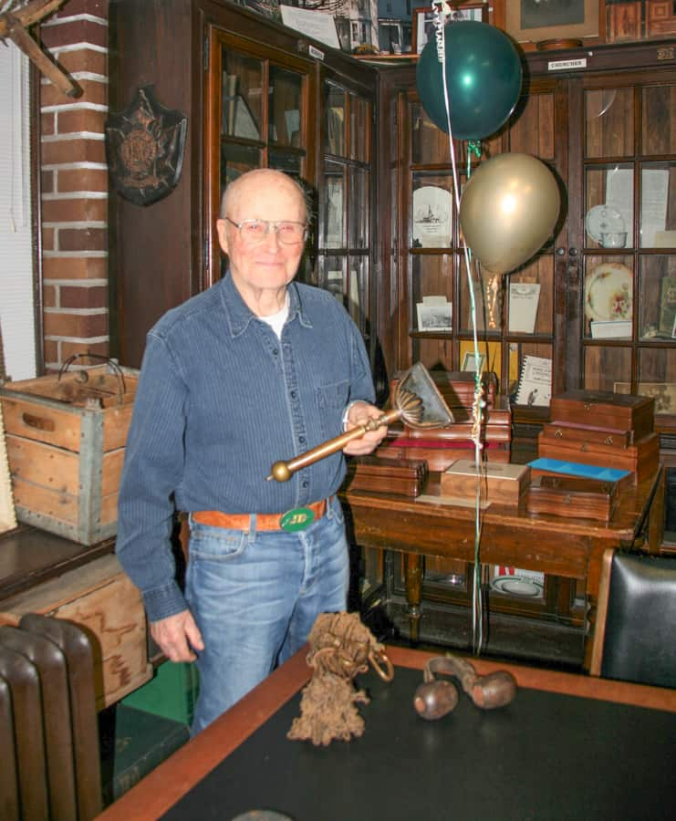 Bill Lake pictured here with a tool to groom horses' manes and tails for shows. In the foreground is a set of chains to survey land and an object to straighten oxen's horns