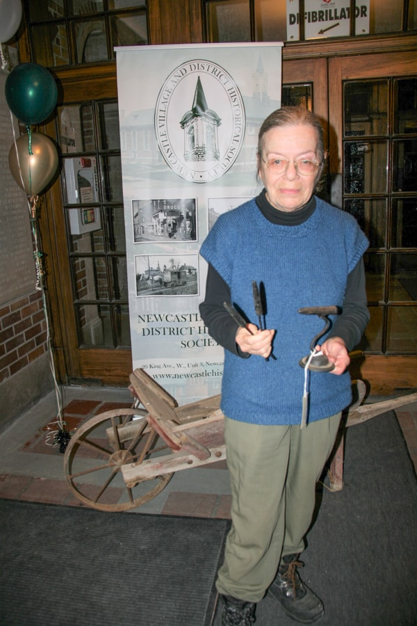 Leslie Wilson holding a goffering iron.In the background is the Watson Wheelbarrow, a recent donation to the society